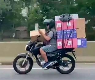 foto: Manejaba su moto con varias cajas y mirando su celular en plena autopista