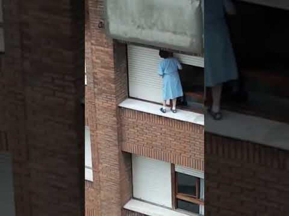 Una mujer que se balancea en la cornisa de un séptimo piso para limpiar la ventana