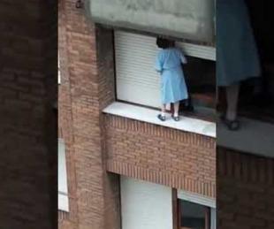 foto: Una mujer que se balancea en la cornisa de un séptimo piso para limpiar la ventana